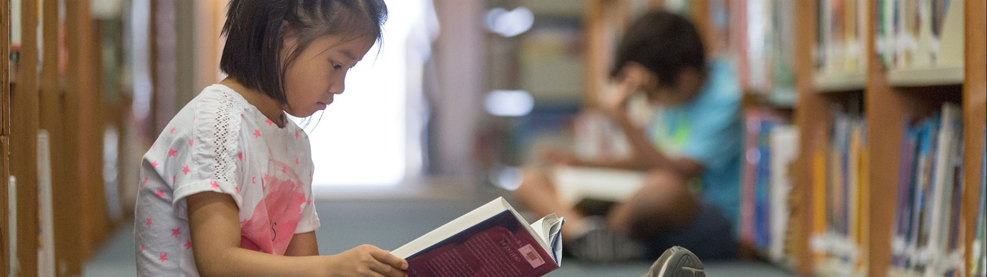 Young asian girl reading a book in a library. Link to: Reading Benefits for Kids and Teens